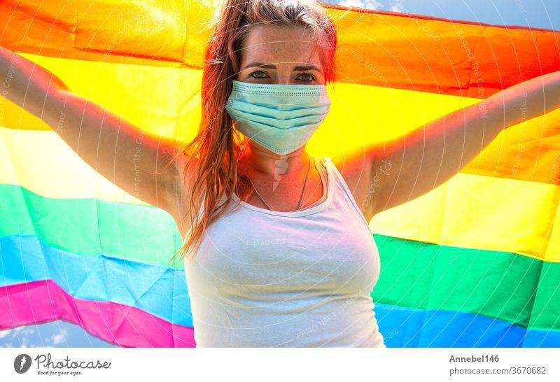 Junge Frau schwenkt Regenbogenfahne für LGBT-Rechte, Freiheit für homosexuelles Lgbtq-Konzept, trägt eine Sicherheitsmaske für Covid-19, Coronavirus. Protestierend