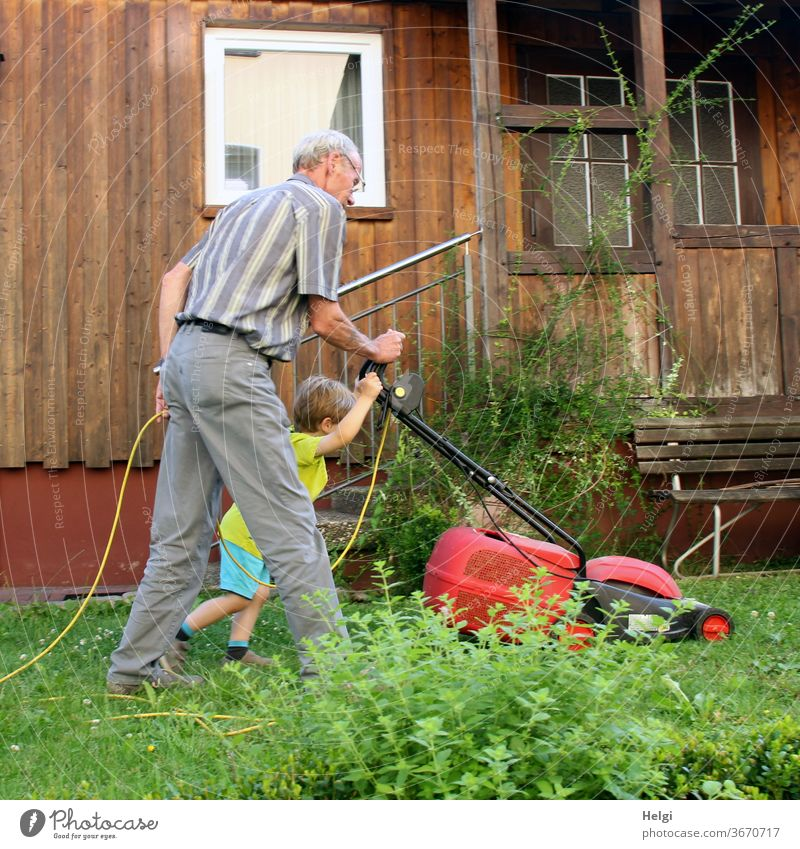 gemeinsam gehts besser - Opa und Enkel mähen den Rasen im Garten | Lieblingsmensch(en) Mensch Senior Kind Kleinkind Mann Großvater Rasenmäher Gras Pflanze Bank