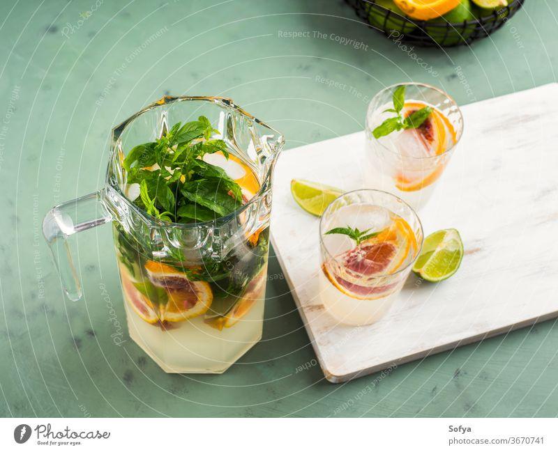 Frisches Sommer-Zitrusgetränk mit Eis auf Grün trinken Zitrusfrüchte Wasser Cocktail Limonade aufgegossen Entzug Mocktail Blutorange Kalk Frucht Saft Minze Soda
