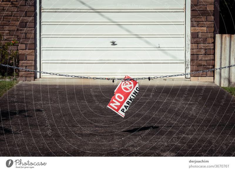 """"""" NO  P A R K I N G """" steht auf einer Garageneinfahrt auf einer absperr Kette . No Parking Parkplatz Schilder & Markierungen Straße Verkehrswege Wege & Pfade"""