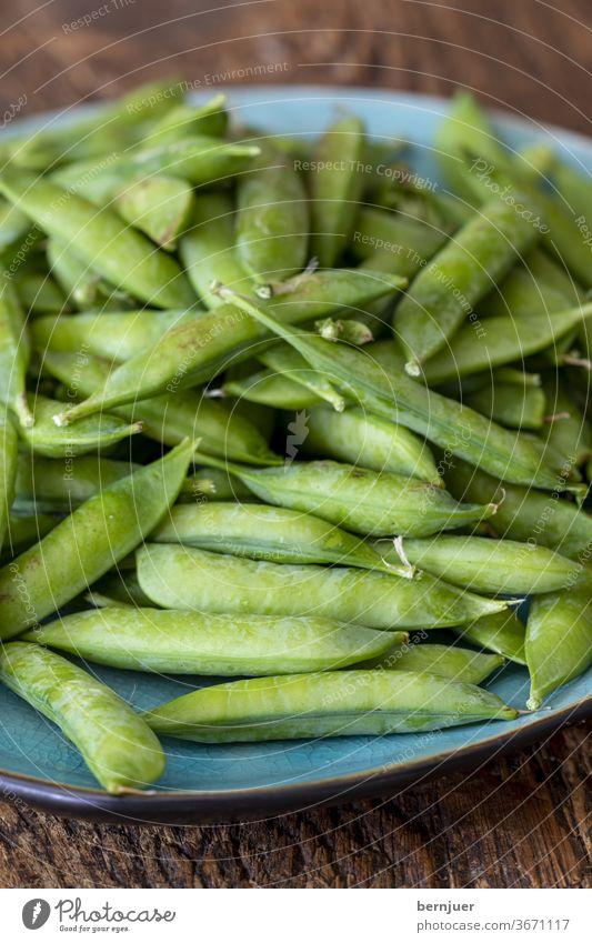 rohe Erbsen auf dunklem Holz Pflanze gesund Legume Lebensmittel Gruppe Bio reifen Gemüse Gourmet Samen Pod frisch Hintergrund Ernährung Vitamin Snack selektiv