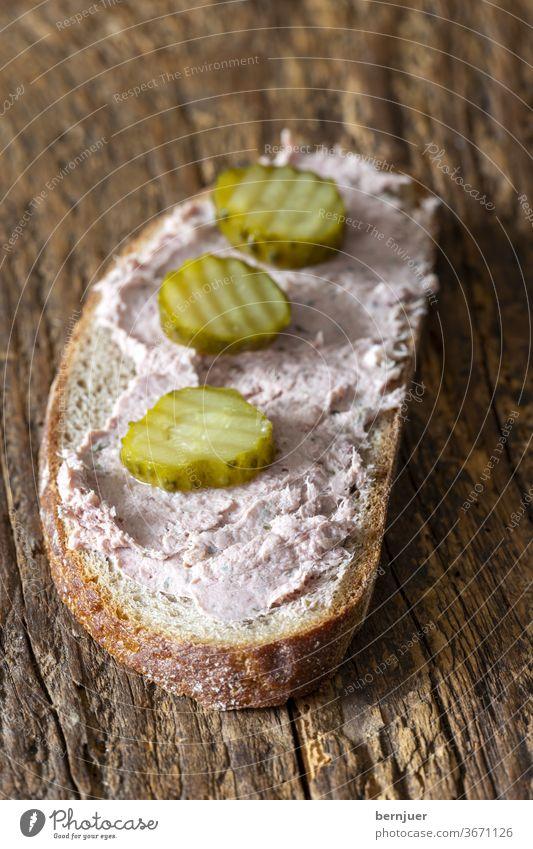 Leberwurstbrot auf dunklem Holz Snack Fleisch Pastete Stück Leberpastete Brot Vollkornbrot Fleischprodukt Wurst traditionell Schweinefleisch Oberansicht Brett