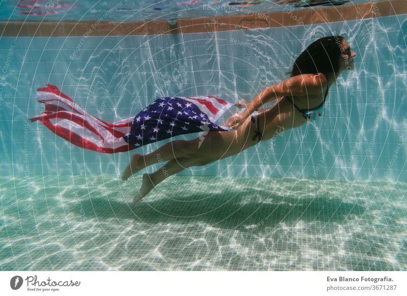 junge Frau in einem Pool, die die amerikanische Flagge unter Wasser hält. Konzept für den Unabhängigkeitstag am 4. Juli. Sommerzeit Stars and Stripes