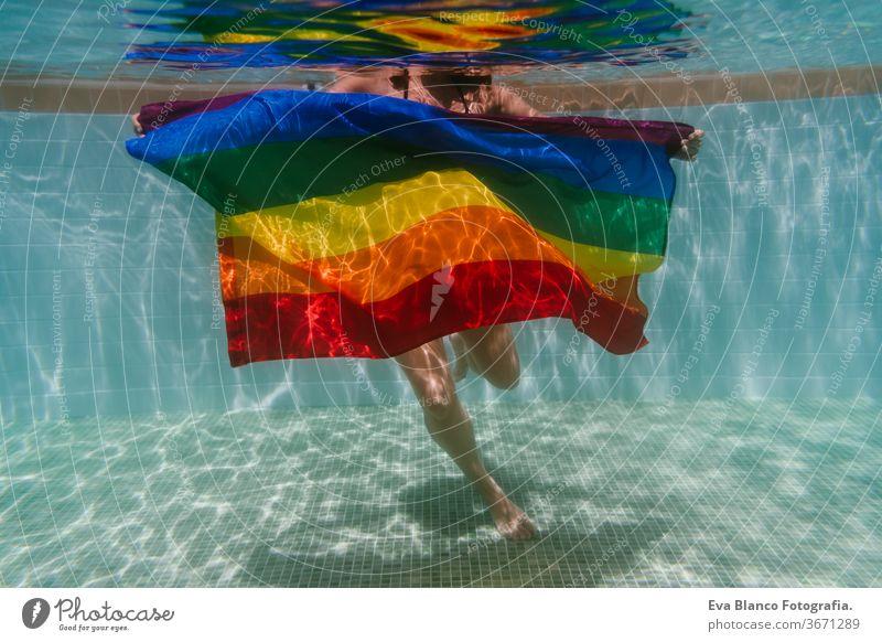 junge Frau in einem Pool, die unter Wasser eine Regenbogenflagge mit schwuler Flagge hält.LGBTQ-Konzept. Sommerzeit Schwimmbad Schwulenflagge lgbtq Beteiligung