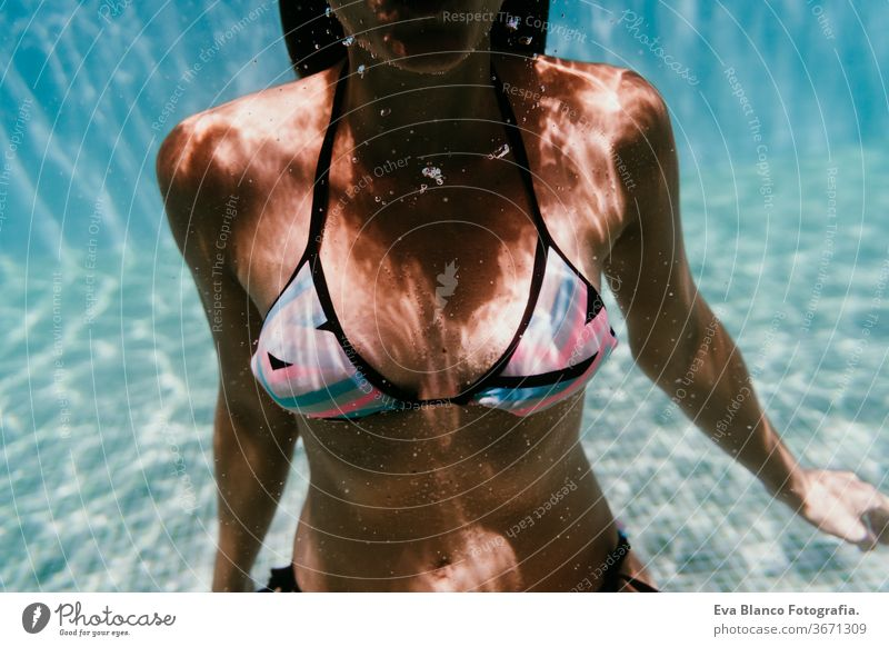 junge Frau, die in einem Schwimmbad unter Wasser taucht. Sommer und lustiger Lebensstil Sonnenbrille Schwimmsport Blasen Spaß Kaukasier Pool Sinkflug Lifestyle