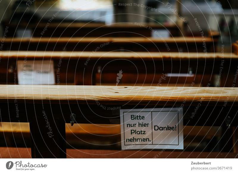 Kirchenbank aus Holz in Kirche mit Schild Platz nehmen wegen Corona Abstand alt Rücksicht Coronavirus Pandemie Infektionsgefahr abstand halten Schutz Religion
