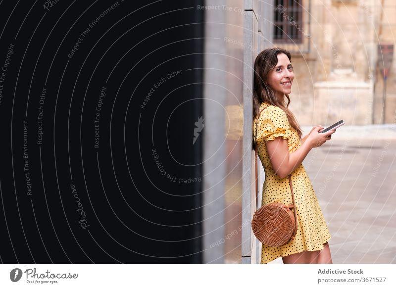 Fröhliche Frau mit Smartphone in der Stadt Großstadt schlendern benutzend Sommer Gebäude urban Lächeln Browsen Kleid heiter Handy online fettarm Surfen Gerät