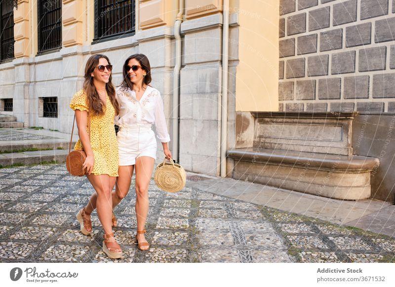 Erfreute Freundinnen gehen die Straße entlang Frauen Spaziergang Großstadt Freundschaft genießen Wochenende Umarmung Zusammensein Freude schlendern Sommer jung