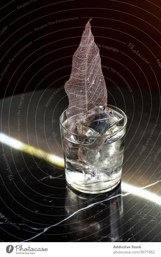 Alkoholisches Getränk mit dekorativem Blatt Cocktail Eis Dekor Bar Tisch kalt Würfel trinken Erfrischung Tasse Glas Party Schnaps durchsichtig Portion dienen