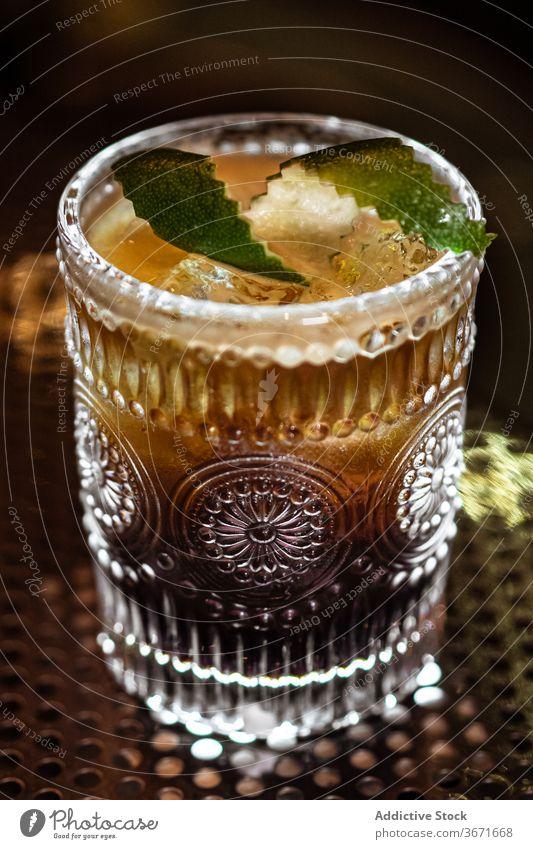 Alkoholisches Getränk mit Limettenschalen Cocktail Bar Kalk Eis sich[Akk] schälen Würfel Locken kalt Tasse Glas Restaurant dunkel Tisch trinken Erfrischung Pub