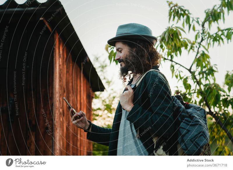 Reisender Mann mit Smartphone auf dem Lande Hipster Browsen reisen ländlich Landschaft benutzend Natur Tourismus männlich Mobile Telefon Surfen Stil Vollbart
