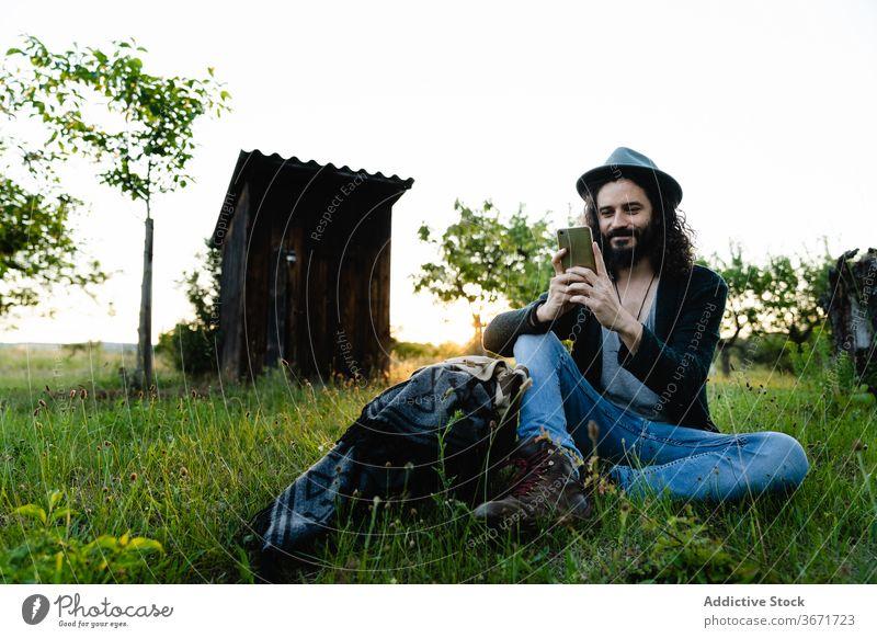 Entspannter Mann, der auf einer Wiese auf seinem Smartphone surft Hipster soziale Netzwerke Talkrunde Feld Sommer sich[Akk] entspannen benutzend männlich Natur