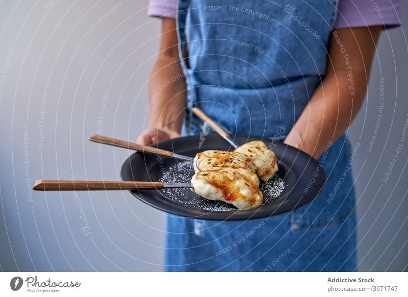 Crop-Frau mit Portionen von Crème brulee auf Teller Dessert lecker Creme Brulee Zucker Koch selbstgemacht geschmackvoll gebacken süß Gebäck Schürze heimwärts