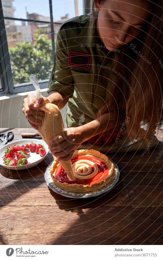 Crop Frau dekorieren Kuchen mit Sahne Spritzbeutel drücken Pasteten Koch Konditorei selbstgemacht lecker Tisch Hausfrau Lebensmittel schmackhaft heimwärts süß
