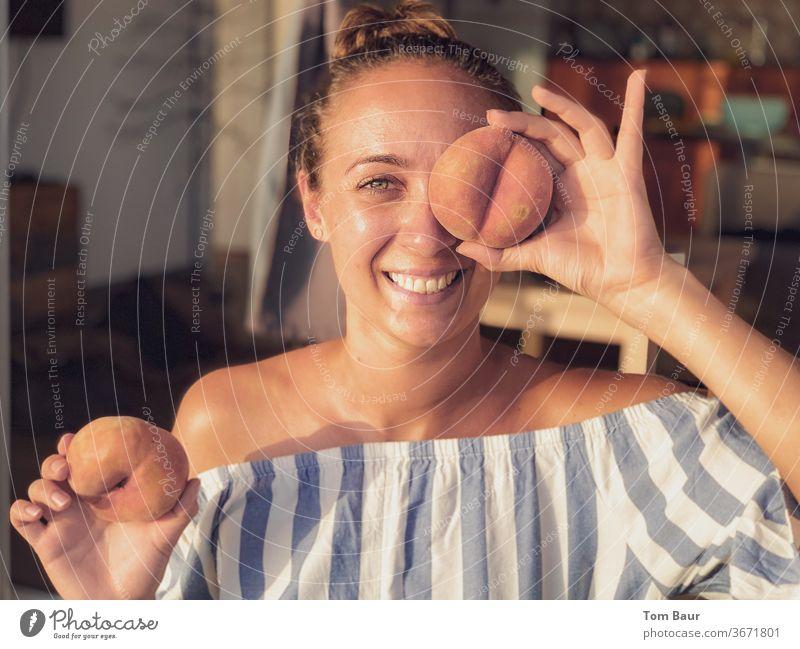 Junge Frau mit brunette Haare hält sich einen Pfirsich vors Auge Brunette lachen happy glücklich spaßig spass blau weiss Porträt Schulter Freizeit & Hobby