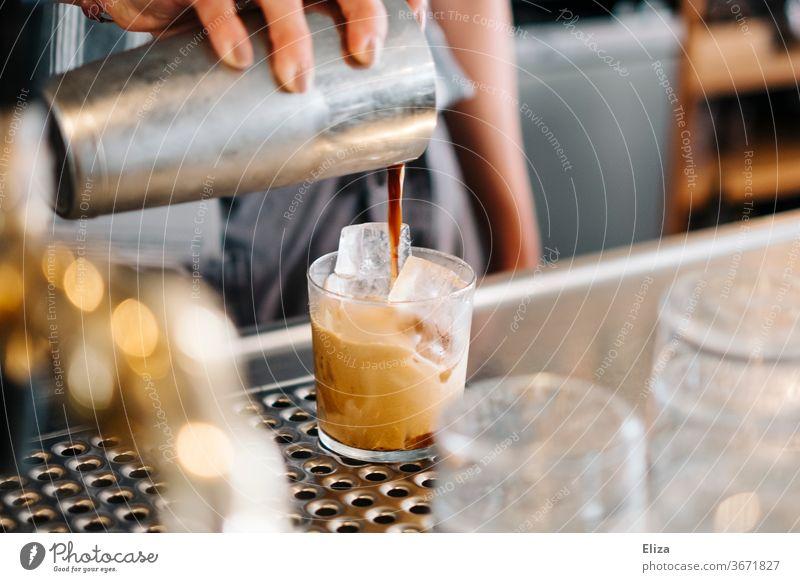 Zubereitung eines kalt gemixten Kaffees auf Eis Eiskaffee geshaked Caffé Freddo bar café gastronomie Getränk Sommer Koffein Shakerato gießen shaker Glas