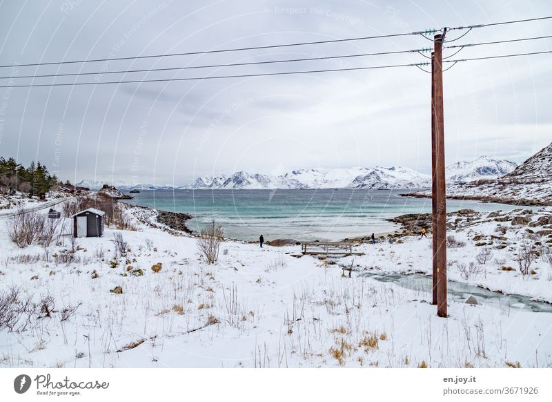 Schneelandschaft an einer Bucht auf den Lofoten Lofoten Inseln Norwegen Skandinavien Winter Kalt Meer Fluss Eis Strand Felsen Urlaub Reise