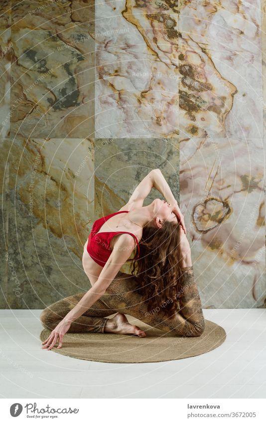 Junge brünette Frau in rotem Top, die drinnen die einbeinige King Pigeon Pose (eka pada rajakapotasana) übt Yoga yogini Sport Athlet schlank jung praktizieren