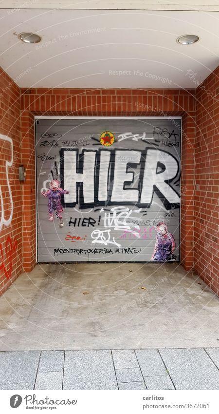 HIER ! Nur damit das klar ist ...... Einfahrt Tor Rolltor Graffiti Schmiererei Garage Garagentor geschlossen Gebäude Wand grau Innenstadt