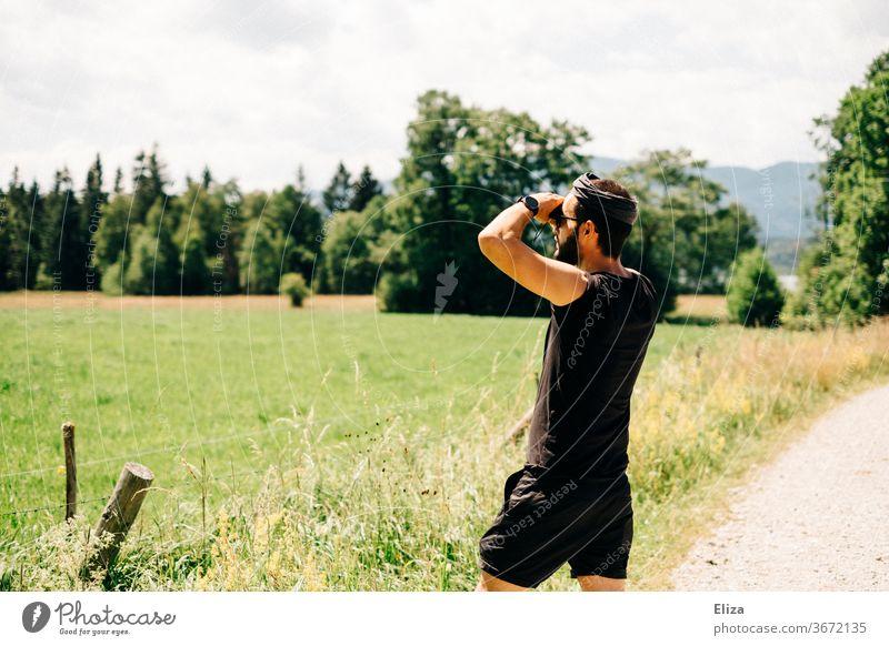 Mann beobachtet etwas durch ein Fernglas in der Natur beobachten suchen Abenteuer Landschaft Sommer Ferne Blick entdecken Aussicht Tourismus Neugier Erwachsene