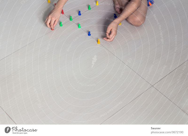Der Junge spielt zu Hause mit seinem bunten Spielzeug und zeigt konzeptionell soziale Distanzierung. Die neue Normalität. im Innenbereich Kindheit neue Normale