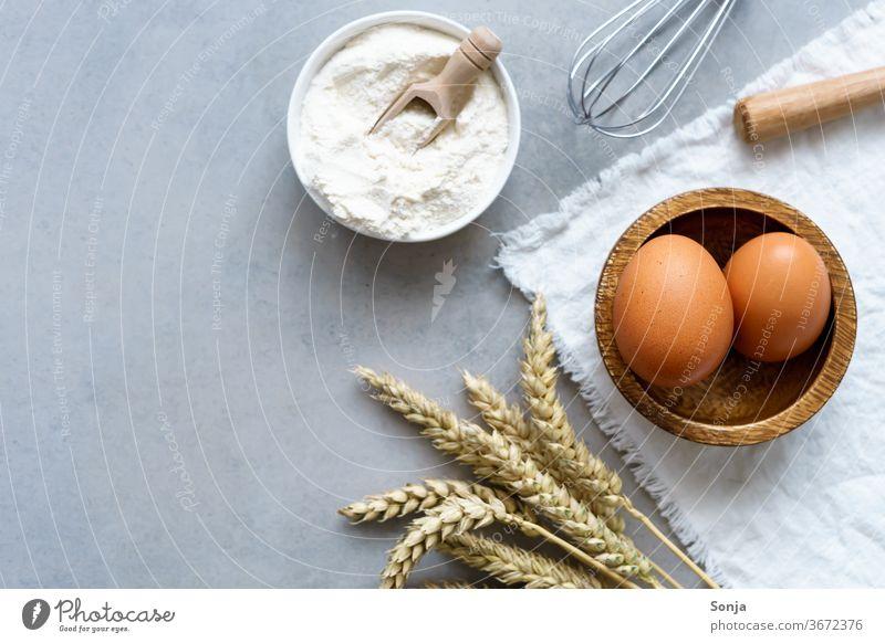 Zutaten für Kuchen und Kekse auf einem grauen Küchentisch. Weizenähre, braune Eier und Mehl, Draufsicht eier Vorbereitung Teigwaren Brot backen roh Backwaren