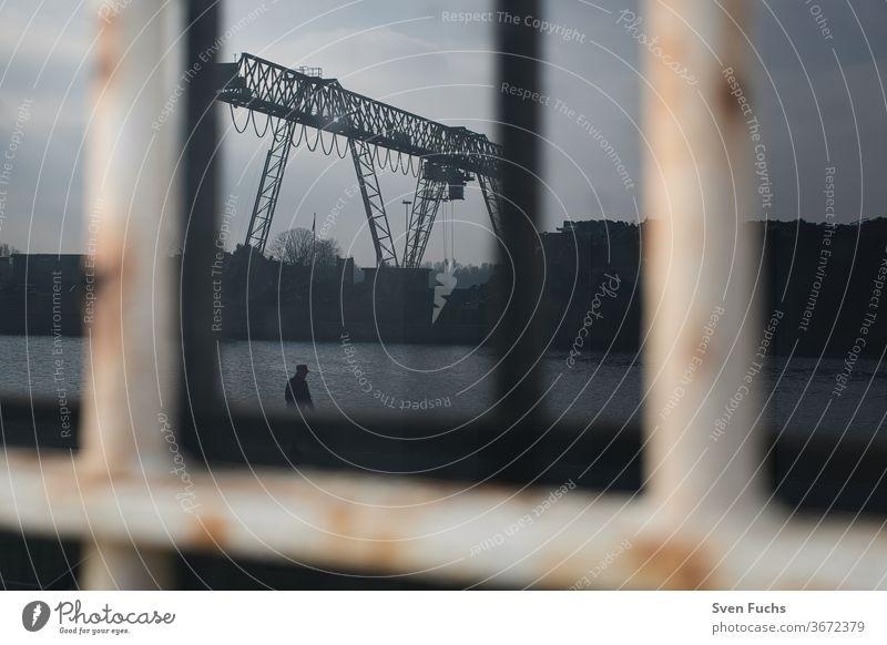 Ein Industriekran spiegelt sich in einer schmutzigen Scheibe. Ein einzelner Mann läuft am Kai vorbei Fensterscheibe Reflektion Landschaft Gebäude Grunge rostig