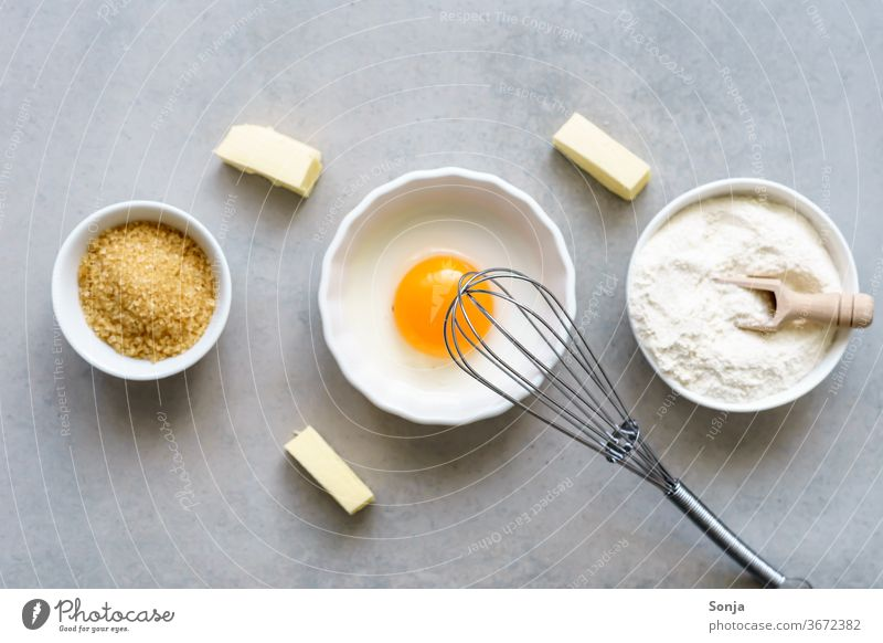 Eidotter, Mehlund Zucker in drei weißen Schüsseln. Backzutaten für Kuchen, Draufsicht. Zutaten eidotter Tisch backen rustikal Teigwaren Lebensmittel Schneebesen