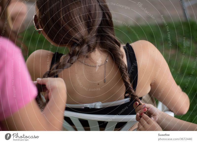 Zöpfe flechten. Mädchen unter sich Sommer Haare Glück Freude Ferien Frisur Spiele Sonne Kindheit Fröhlichkeit Natur Zusammen Zusammensein