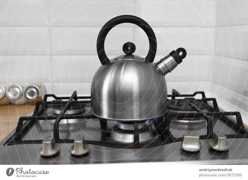 Metallkessel auf einem Gasherd. Kessel kocht auf einem Gasherd. Fokus auf einen Ausguss. Teekessel mit kochendem Wasser auf einem Gasherd Wasserkessel Herd