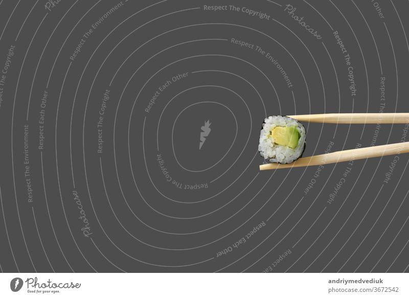frische vegetarische Maki-Sushi-Rolle mit isolierten Holzstäbchen auf grauem Hintergrund. rollen Lebensmittel Granele maki Sea Bass Sashimi Wasabi vereinzelt