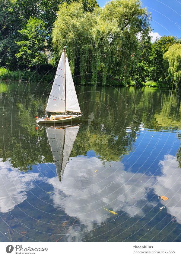 Ein Modellsegelboot segelt an einem Sommertag auf einem Weiher Segel Boot Segelboot Modellbau Wolken im Wasser Weiden Miniatur Segeln
