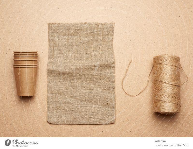 Pappbecher, Strang mit braunem Seil und leerer Tasche auf braunem Holzgrund Konzept Accessoire Hintergrund beige blanko Sackleinen Leinwand Nahaufnahme Stoff