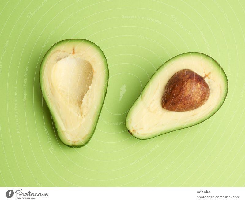halbreife grüne Avocado mit braunem Kern auf grünem Hintergrund Ausschnitt Nahaufnahme Farbe Essen zubereiten Kerngehäuse geschnitten lecker Diät exotisch