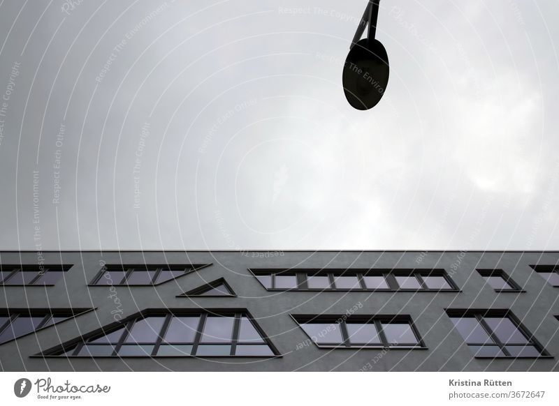 modernes gebäude und eine laterne mit grauem wolkenhimmel haus architektur fassade bürogebäude fenster stadt städtisch immobilie urban abstrakt bewölkt spitz