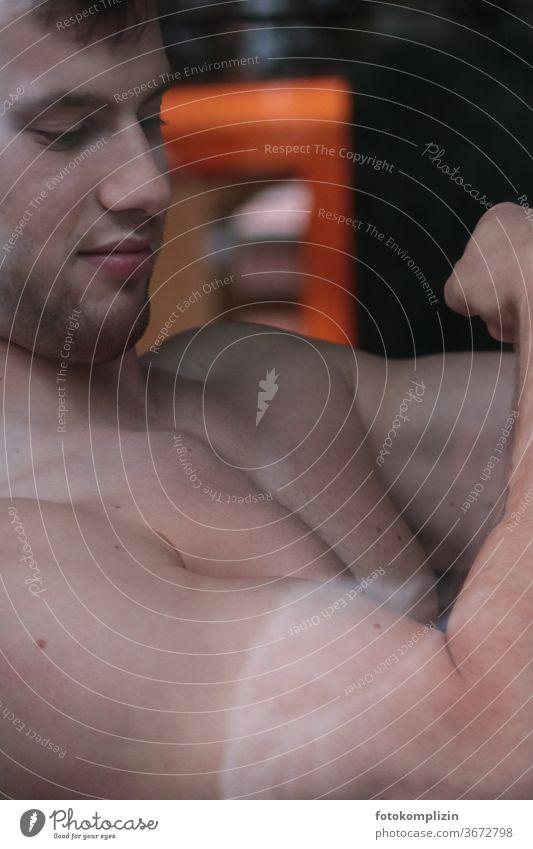 junger Mann spannt Oberarm-Muskel an muskulös Training Junger Mann stark Fitness Stärke Körperbewusstsein Bodybuilding Übung männlich aktiv Fitnessstudio Athlet