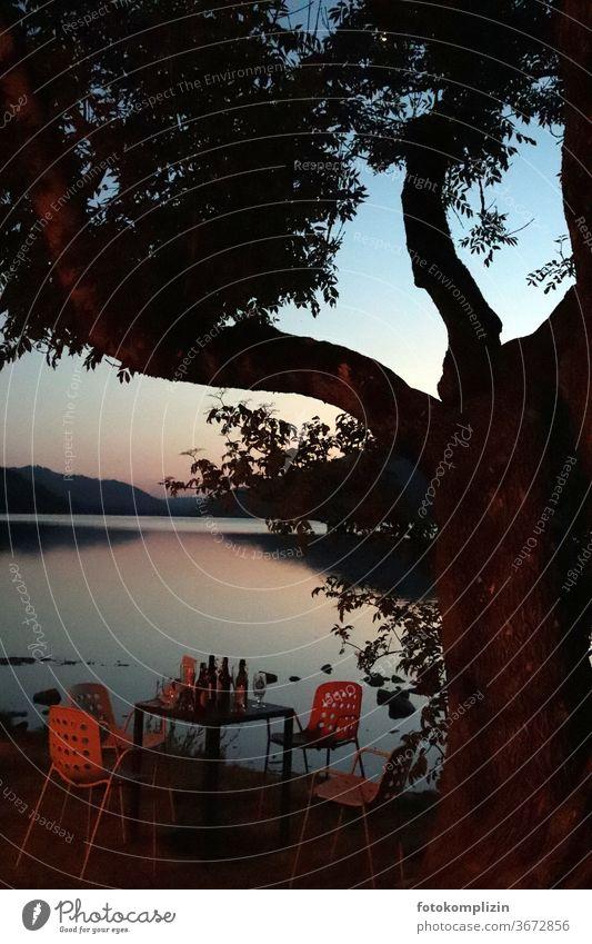 verlassener Tisch mit Flaschen, Gläser und Stühlen neben einem Baum an einem stillen See in Abenddämmerung Feierabend Abendlicht Sonnenuntergangsstimmung