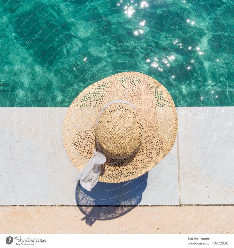Frau mit großem Sommersonnenhut entspannt sich am Pier am klaren türkisfarbenen Meer. Wasser Sonne Hut Freizeit Schönheit Mädchen Person blau Bräune Körper jung