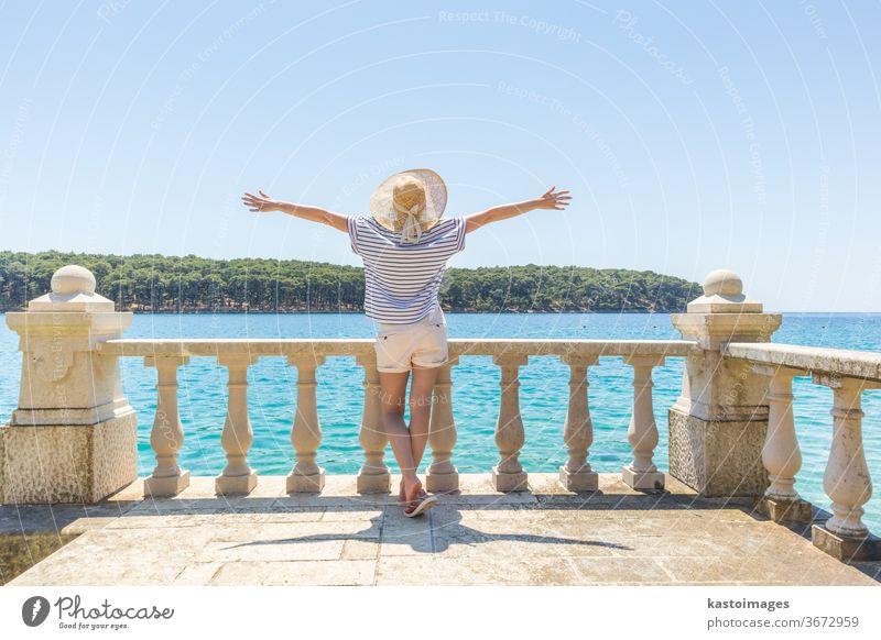 Rückansicht einer glücklichen Frau im Urlaub, die einen Strohhut trägt, auf einem luxuriösen, eleganten, alten Steinbalkon einer Küstenvilla steht, sich entspannt, die Arme zur Sonne erhoben und auf das blaue Adriatische Meer schaut.