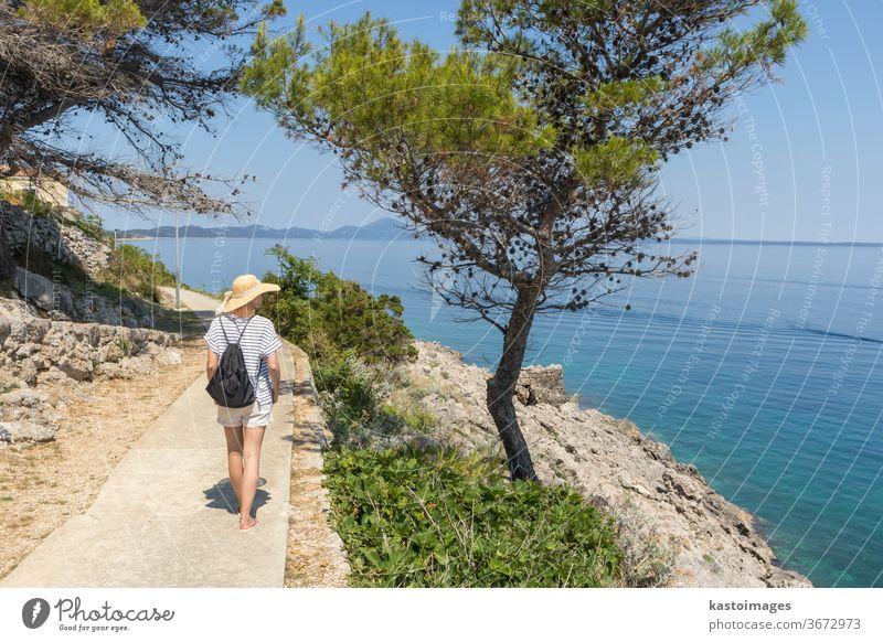 Junger aktiver Feamle-Tourist mit kleinem Rucksack, der auf einem Küstenweg zwischen Pinienbäumen wandert und nach einer abgelegenen Bucht sucht, um allein in Ruhe am Meer in Kroatien zu schwimmen. Reise- und Abenteuerkonzept.