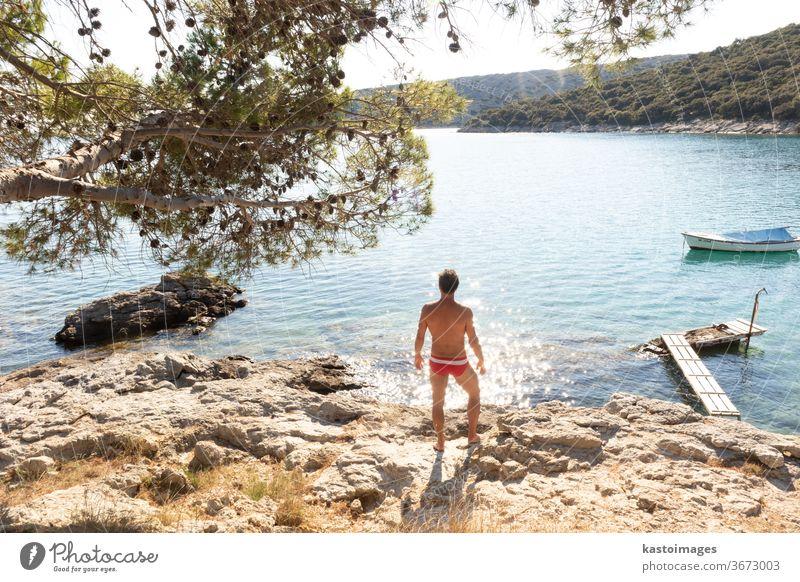 Rückansicht eines Mannes in roter Badehose, der sich an einer wilden Bucht der Adria an einem Strand im Schatten eines Kiefernwaldes sonnen und entspannen will. Konzept einer entspannten gesunden Lebensweise.