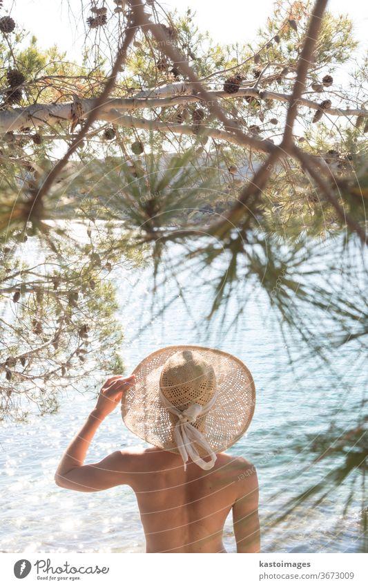 Rückansicht einer oben ohne schönen Frau mit nichts als einem Strohhut, die sich an der wilden Küste der Adria an einem Strand im Schatten einer Pinie entspannt. Entspanntes Konzept eines gesunden Lebensstils.