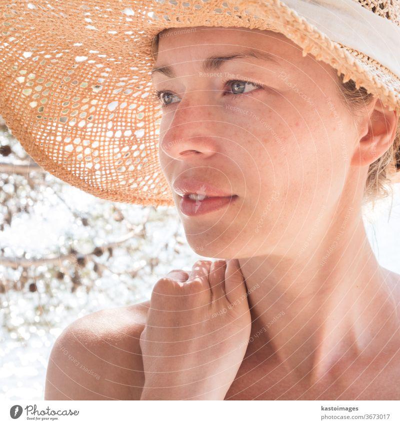 Nahaufnahme-Porträt einer ungeschminkten, natürlich schönen, sinnlichen Frau mit Stroh-Sonnenhut am Strand im Schatten einer Pinie. Sommer Person Dame jung MEER