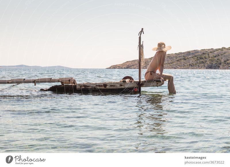 Blick auf eine nicht wiederzuerkennende Frau mit großem Sommersonnenhut, die sich oben ohne bräunt und auf einem alten Holzsteg in einer abgelegenen ruhigen Bucht an der kroatischen Adria entspannt.