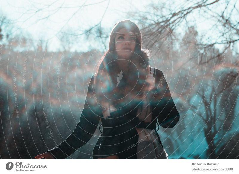 Attraktive Brünette in Winterkleidung und orangem Kopftuch, die an einem kalten Wintertag in die Ferne blickt. Wassertropfen, die überall hinfliegen und einen Nebel, Nebel und Mini-Regenbögen erzeugen