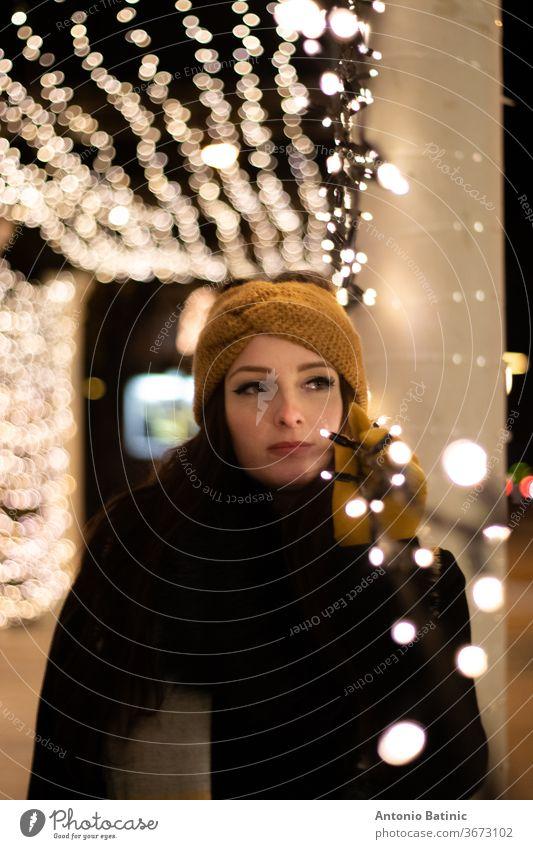 Nachtporträt einer jungen Frau, die in die Ferne schaut und sich an eine Lichterkette lehnt. Kalte Winternacht Lächeln Bokeh Mädchen schön Abend Porträt