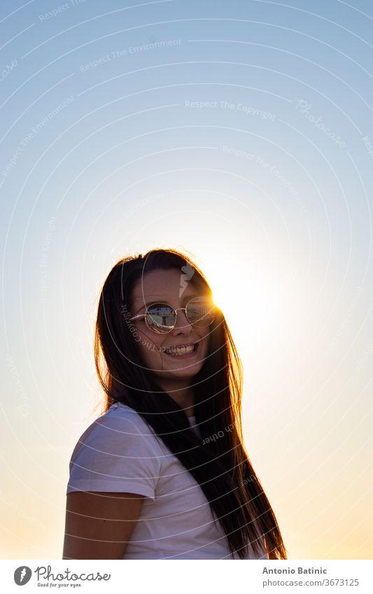 Attraktive Brünette mit Sonnenbrille lachend , Sonne direkt hinter dem Kopf spähend, goldene Sonnenuntergangsstunde. attraktiv Hintergrund schön Schönheit