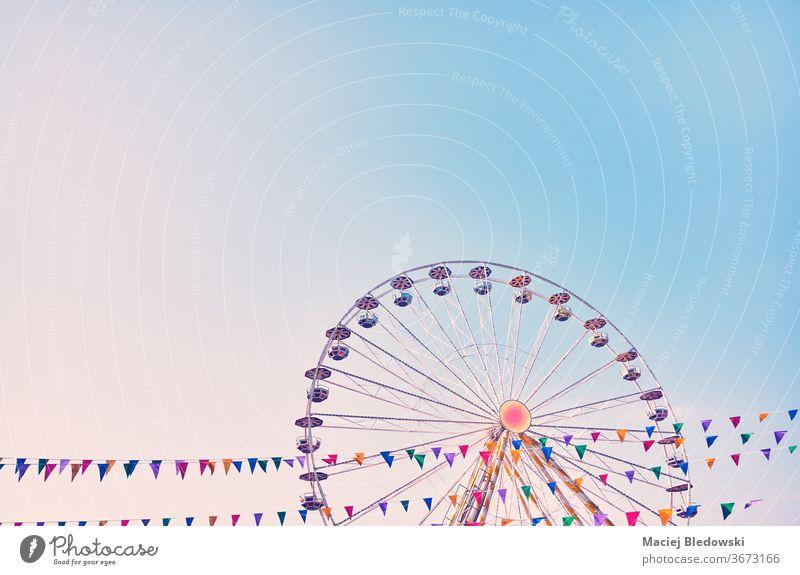 Riesenrad mit wolkenlosem Himmel im Hintergrund. ferris Rad Vergnügen Park Spaß Mitfahrgelegenheit Kindheit retro rosa Instagrammeffekt Nostalgie Entertainment
