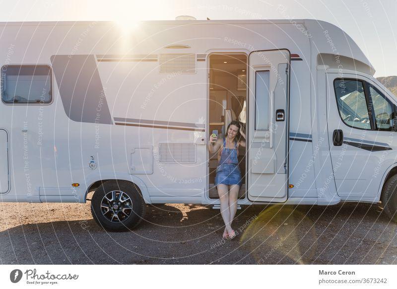 Lächelnde junge Frau, die an einem sonnigen Tag ein Selfie auf ihrem am Strand geparkten Wohnmobil mitnimmt Lebensstile Kleintransporter wüst Erkundung Reise