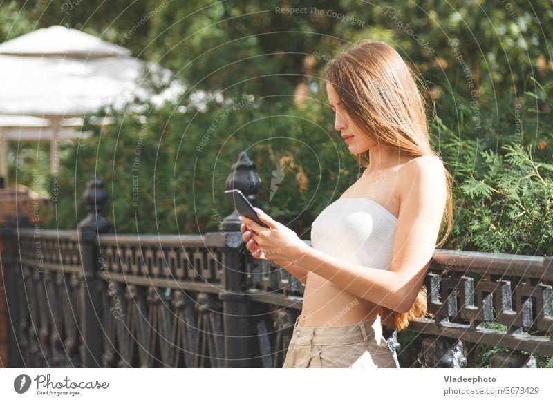 Junge stilvolle hübsche Frau mit Smartphone in den Straßen der Stadt. jung Großstadt stylisch Hut Europa Technik & Technologie Glück Mädchen urban Menschen